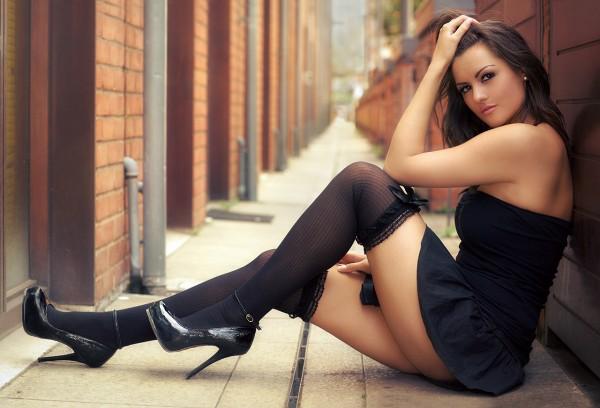 Девушка в черных чулках сидит у стены
